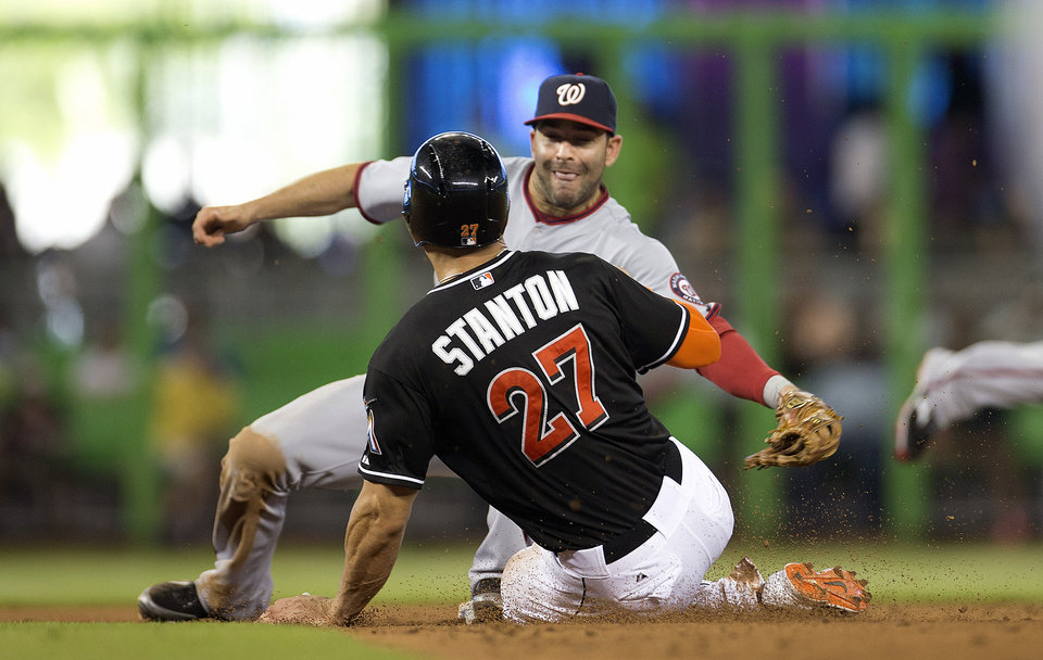 Photo - Miami Marlins runner Giancario Stanton (8) steals second and then goes to third after Washington Nationals' Danny Espinosa, rear, misplayed the ball during the sixth inning of a baseball game in Miami, Wednesday, July 30, 2014. The Nationals won 4-3. (AP Photo/J Pat Carter)