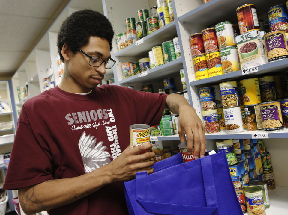 Photo - Eugene (not permitted to use last name) is shown filling bags in the food pantry. This year is the 40th anniversary of Youth Services of Oklahoma County.  SKIL is one of their programs that allows youth to live independently.   Photo taken Tuesday,  May, 14, 2013. Photo  by Jim Beckel, The Oklahoman.