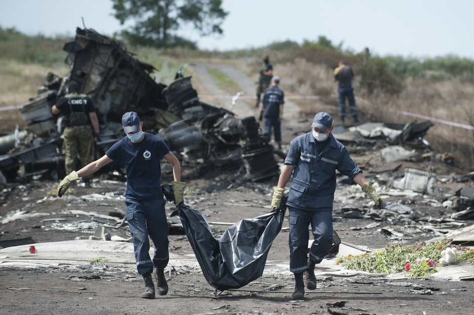 Photo - Ukrainian Emergency workers carry a victim's body in a body bag as pro-Russian fighters stand in guard at the crash site of Malaysia Airlines Flight 17 near the village of Hrabove, eastern Ukraine, Sunday, July 20, 2014. Rebels in eastern Ukraine took control Sunday of the bodies recovered from downed Malaysia Airlines Flight 17, and the U.S. and European leaders demanded that Russian President Vladimir Putin make sure rebels give international investigators full access to the crash site.(AP Photo/Evgeniy Maloletka)