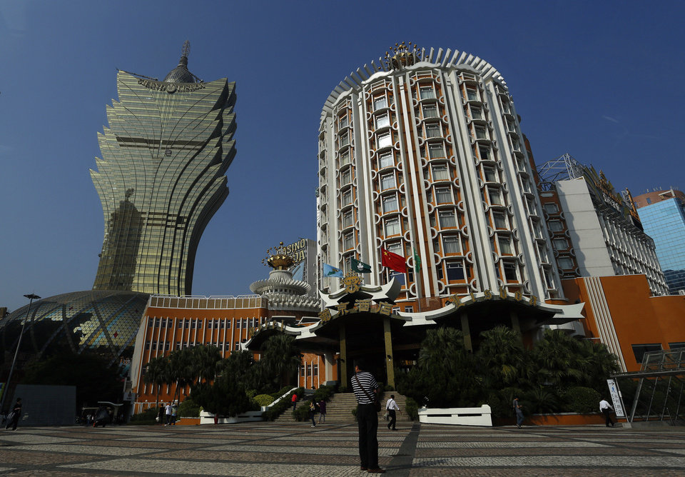 Photo - In this May 25, 2012 photo, the new, left, and old Casino Lisboa, right, are seen in Macau. Macau is in the midst of one of the greatest gambling booms the world has ever known. To rival it, Las Vegas would have to attract six times as many visitors  essentially every man, woman and child in America. Wynn Las Vegas now makes nearly three-quarters of its profits in Macau. Sands, which owns the Venetian and Palazzo, earns two-thirds of its revenue there. (AP Photo/Vincent Yu)