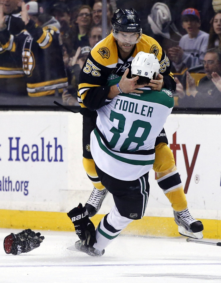 Photo - Boston Bruins defenseman Johnny Boychuk (55) fights with Dallas Stars center Vernon Fiddler (38) during the first period of an NHL hockey game in Boston on Tuesday, Nov. 5, 2013. (AP Photo/Elise Amendola)