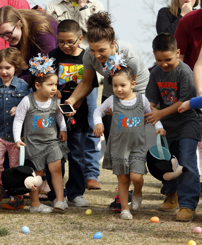 Twins Nanaiya and Nevaeh Mantaghi, 3, get help from brothers Rudy, 8, Isaiah, 7, and mother Samantha at the Cleveland County YMCA Community Easter Egg Hunt on Saturday, March 30, 2013 in Norman, Okla. Photo by Steve Sisney, The Oklahoman