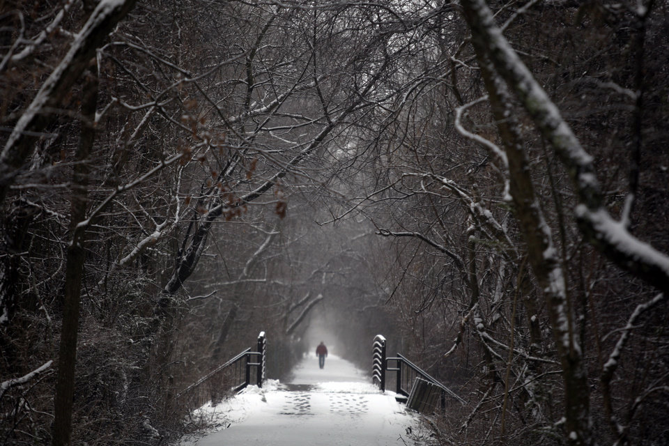 Photo - Rayburn Vandergrift walks along the snowy and misty Huckleberry Trail after a winter storm deposited snow in Blacksburg Va., Friday, Feb. 8, 2013. (AP Photo/The Roanoke Times, Matt Gentry)