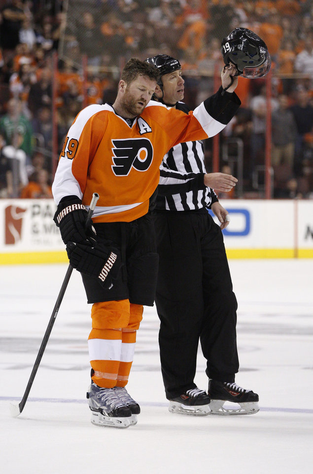 Photo - Philadelphia Flyers' Scott Hartnell-tips his helmet to the crowd as he is escorted off the ice by linesman Pierre Racicot, right, after receiving a five-minute penalty for spearing and a 10-minute game misconduct during the third period of an NHL hockey game against the Carolina Hurricanes, Sunday, April 13, 2014, in Philadelphia. The Hurricanes won 6-5 in a shootout. (AP Photo/Chris Szagola)