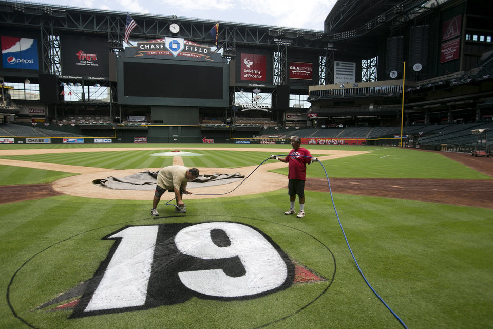 "Diamondbacks head groundskeeper Grant Trenbeath, right paints a ""19"" logo honoring the fallen firefighters from the Yarnell Hill Fire as assistant groundskeeper Manny Lugo holds the paint hose, behind home plate at Chase Field in Phoenix, on Thursday July 4, 2013.  (AP Photo/The Arizona Republic, Davlid Wallace)  MARICOPA COUNTY OUT; MAGS OUT; NO SALES"