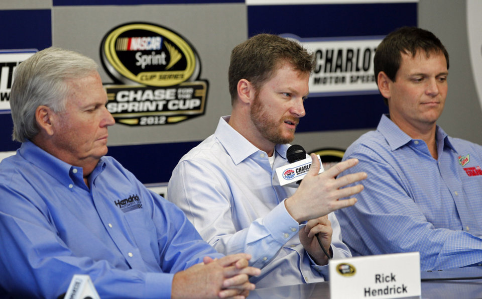 Photo -   Dale Earnhardt Jr, center, talks about missing the next two races with his second concussion in the past six weeks as team owner Rick Hendrick, left, and crew chief Steve Letarte, right, look on during a news conference prior to practice for Saturday's NASCAR Bank of America 500 NASCAR Sprint Cup series auto race in Concord, N.C., Thursday, Oct. 11, 2012. (AP Photo/Terry Renna)