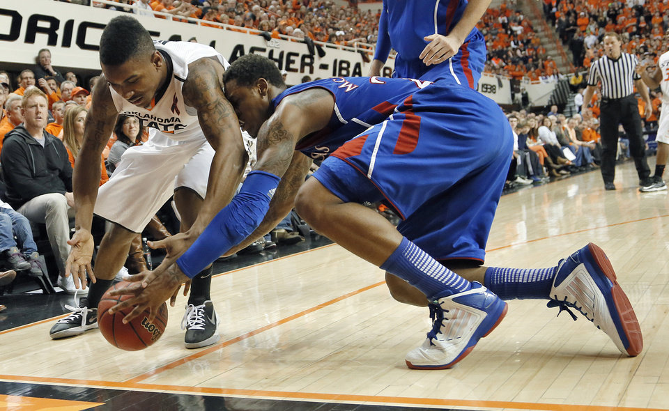 Photo - Oklahoma State 's Le'Bryan Nash (2) and Kansas' Ben McLemore (23) fight for a loose ball during the college basketball game between the Oklahoma State University Cowboys (OSU) and the University of Kanas Jayhawks (KU) at Gallagher-Iba Arena on Wednesday, Feb. 20, 2013, in Stillwater, Okla. Photo by Chris Landsberger, The Oklahoman