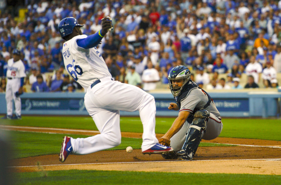 Photo - Los Angeles Dodgers' Yasiel Puig, left, scores on a double by Adrian Gonzalez as Atlanta Braves catcher Evan Gattis takes a late throw during the first inning of a baseball game, Thursday, July 31, 2014, in Los Angeles. (AP Photo/Mark J. Terrill)