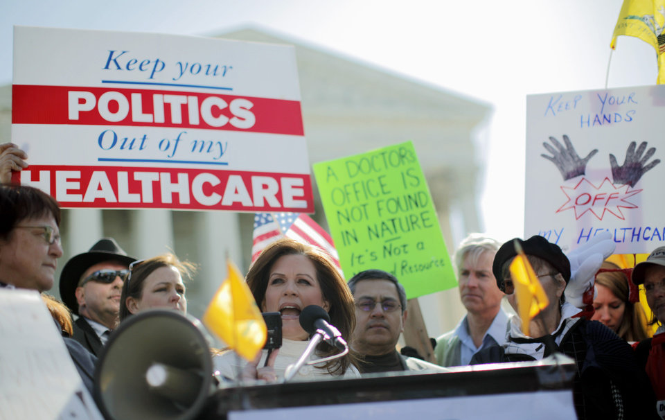 Photo - Rep. Michele Bachmann, R-Minn., addresses Tea Party supporters and opponents of health care reform in front of the Supreme Court in Washington, Tuesday, March 27, 2012, as arguments continue on the health care law signed by President Barack Obama. (AP Photo/Charles Dharapak) ORG XMIT: DCCD110