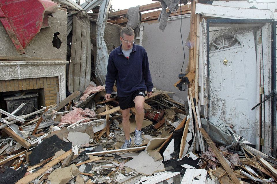 Photo - John Boxmeyer climbs through the rubble of a home where he was helping friends recover belongings on Thursday, April 28, 2011, in Tuscaloosa, Ala. The storm demolished a neighborhood near the University of Alabama campus. (AP Photo/Jay Reeves)