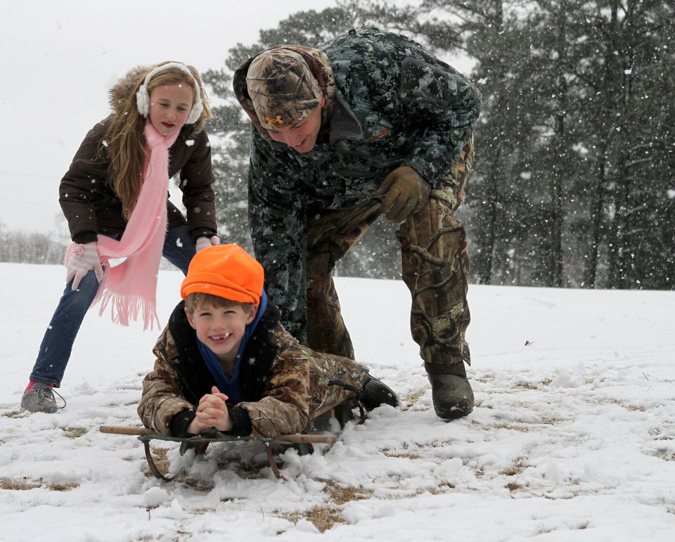 Photo - Sarah Paige Shirley, left, watches as L. J. Fruge´ pushes his son, Jay, down a hill in the snow Thursday, Jan. 17, 2013, at Northwood Country Club in Meridian, Miss. The snow that lightly covered the area was all melted by late morning. (AP Photo/The Meridian Star, Paula Merritt)