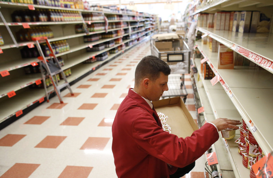 Photo - Market Basket employee Mark Feole, of Methuen, Mass., restocks shelves at a Market Basket supermarket location, Thursday, Aug. 28, 2014, in Chelsea, Mass. A six-week standoff between thousands of employees of the New England supermarket chain and management has ended with the news that beloved former CEO Arthur T. Demoulas is back in control after buying the entire company. (AP Photo/Steven Senne)