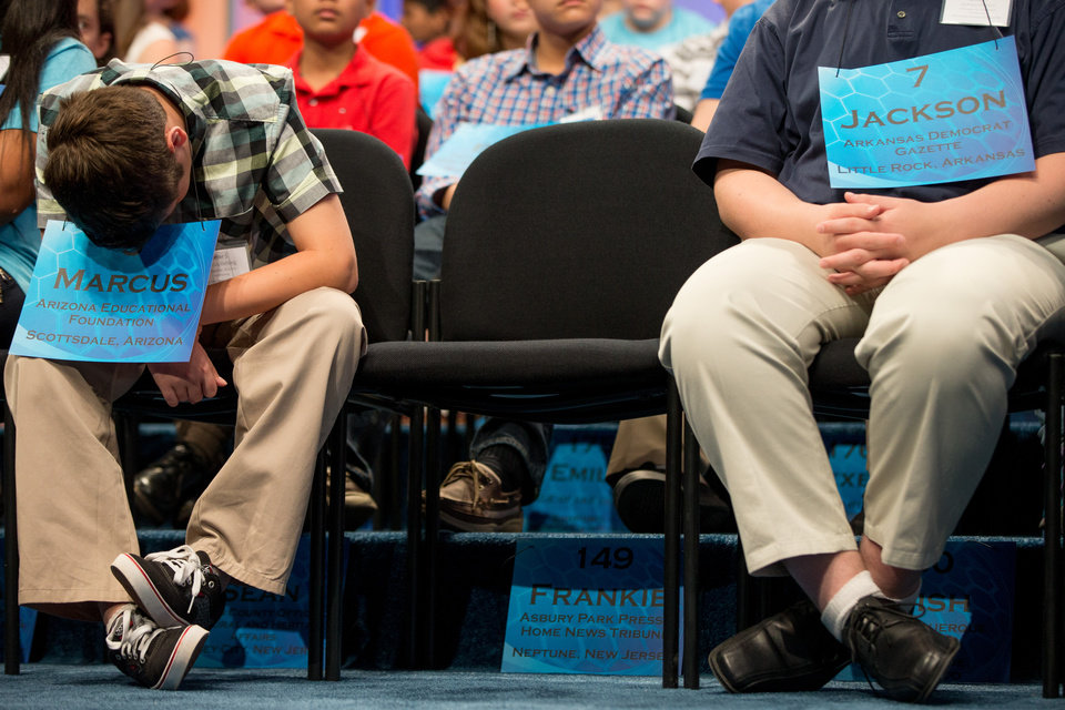 Photo - Marcus Behling, 13, of Scottsdale, Ariz., left, struggles to stay away during the 2015 Scripps National Spelling Bee, Wednesday, May 27, 2015, in Oxon Hill, Md. Also pictured is Jackson Parker, 14, of Little Rock, Ark. right. (AP Photo/Andrew Harnik)