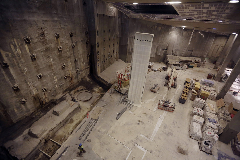 Photo - The slurry wall, left, part of the World Trade Center's original foundation and the last column removed from the WTC site, center covered in a protective wrap, are seen during a media tour of the National September 11 Memorial and Museum, Friday, Sept. 6, 2013 in New York. Construction is racing ahead inside the museum as the 12th anniversary of the Sept. 11, 2001 attacks draws near. Several more large artifacts have been installed in the cavernous space below the World Trade Center memorial plaza. (AP Photo/Mary Altaffer)