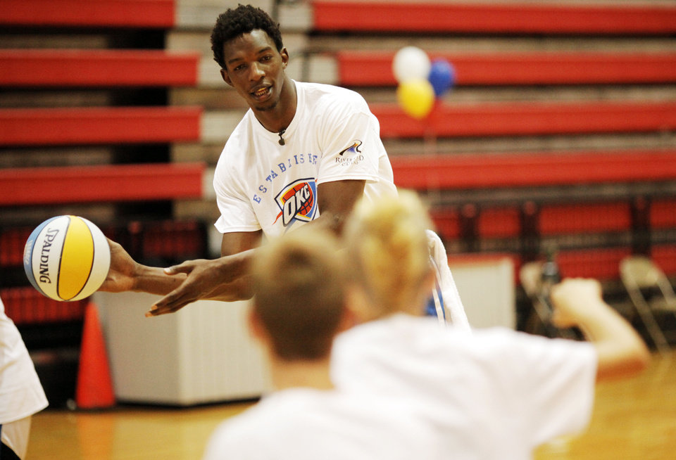 Photo - Hasheem Thabeet, center for the Oklahoma City Thunder, throws a pass to young campers doing a basketball drill at the Thunder basketball camp at Carl Albert High School in Midwest City on June 25, 2013. Photo by KT KING, The Oklahoman