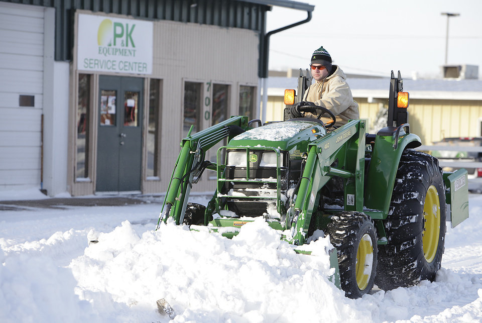 Photo - Service Manager Nick Huntley clears the parking lot at P&K Equipment in Edmond, Wednesday, February 2, 2011.     P&K is the John Deere tractor dealership in Edmond and Huntley said they had several call from parts from folks who are removing snow and broke down.         Photo by David McDaniel, The Oklahoman