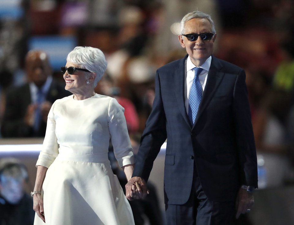 Photo - Senate Minority Leader Harry Reid of Nev., is escorted to the podium by wife Landra before speaking during the third day of the Democratic National Convention in Philadelphia , Wednesday, July 27, 2016. (AP Photo/Paul Sancya)