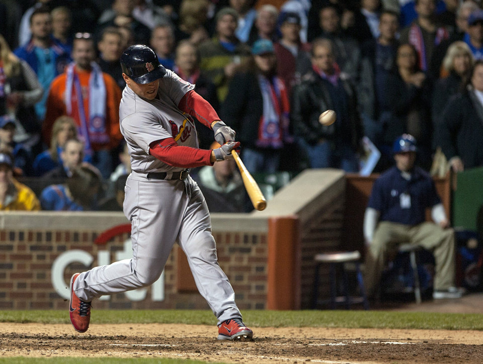 Photo -   St. Louis Cardinals' Matt Holliday hits a two-run home run during the eighth inning of a baseball game against the Chicago Cubs in Chicago on Tuesday, April 24, 2012. (AP Photo/Charles Cherney)