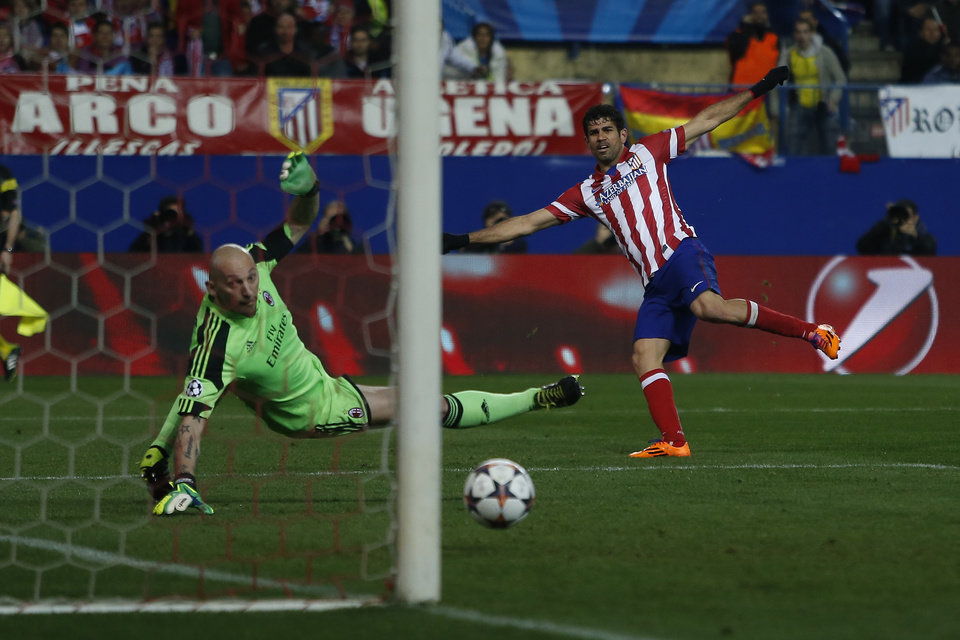 Photo - Atletico's Diego Costa, right, scores his goal during a Champions League last 16 second leg soccer match between Atletico Madrid and AC Milan, at the Vicente Calderon stadium in Madrid, Tuesday, March 11, 2014. (AP Photo/Andres Kudacki)