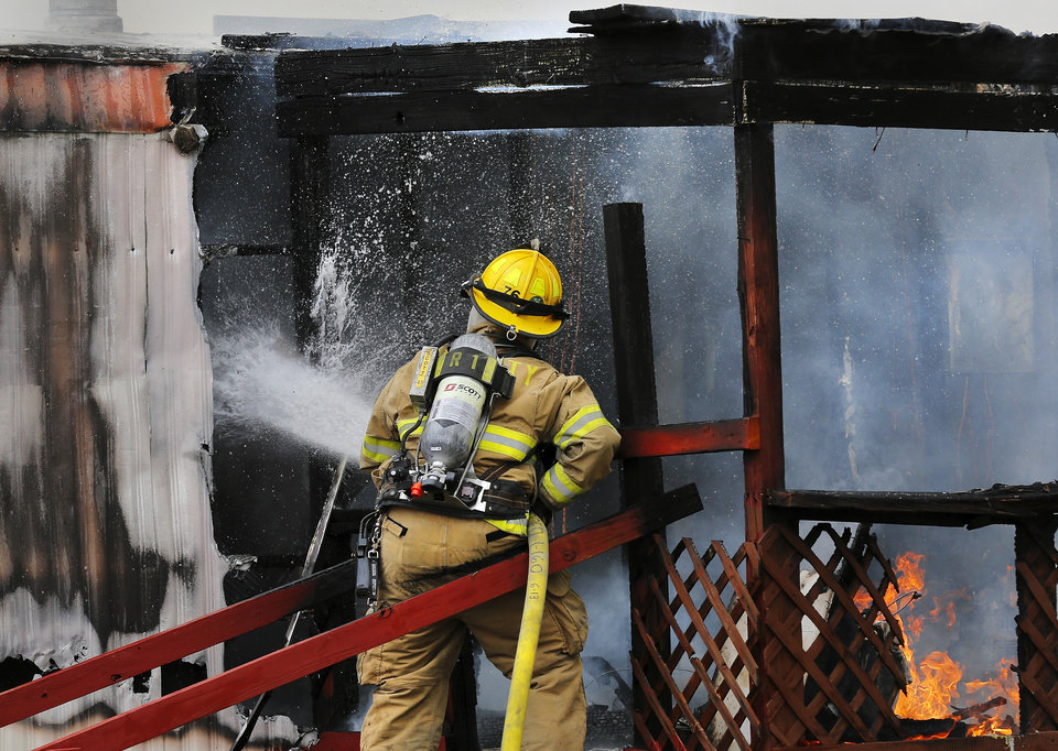 A blaze destroyed a trailer in the Skyline Mobile Home Park on E. Reno and Eastbrook Terrace in Del City on Thursday, June 26, 2014. Del City firefighters put out the fire before it could spread to adjoining properties. The park manager joined neighbors in helping two women and a dog escape from the flames. Theyran to the trailer and pulled a middle-aged woman and her elderly mother, who is confined to a wheelchair, from the home as flames leaped from windows and the roof and dark gray smoke rose into the air. A pet dog was saved but another dog perished in the fire. Photo by Jim Beckel, The Oklahoman
