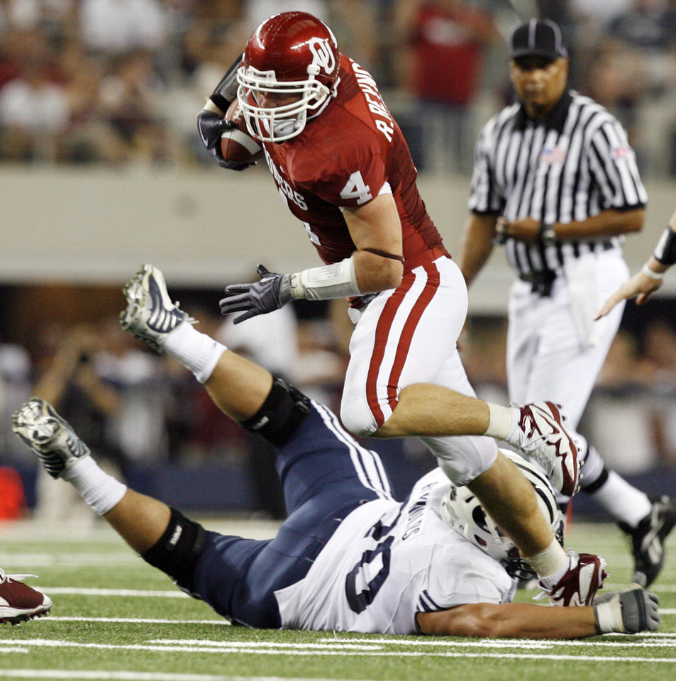 Photo - OU's Ryan Reynolds (4) is tripped up on an interception return by BYU's Matt Reynolds (70) in the first quarter during the college football game between the Brigham Young University Cougars (BYU) and the University of Oklahoma Sooners (OU) at Cowboys Stadium in Arlington, Texas, Saturday, September 5, 2009. By Nate Billings, The Oklahoman ORG XMIT: KOD