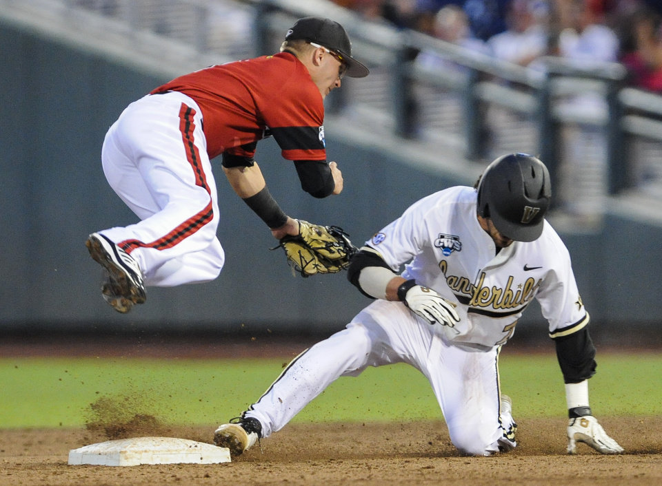Photo - Vanderbilt's Dansby Swanson, right, steals second base against Louisville shortstop Sutton Whiting, left, and advances to third base on a throwing error in the fourth inning of an NCAA baseball College World Series game in Omaha, Neb., Saturday, June 14, 2014. (AP Photo/Dave Weaver)