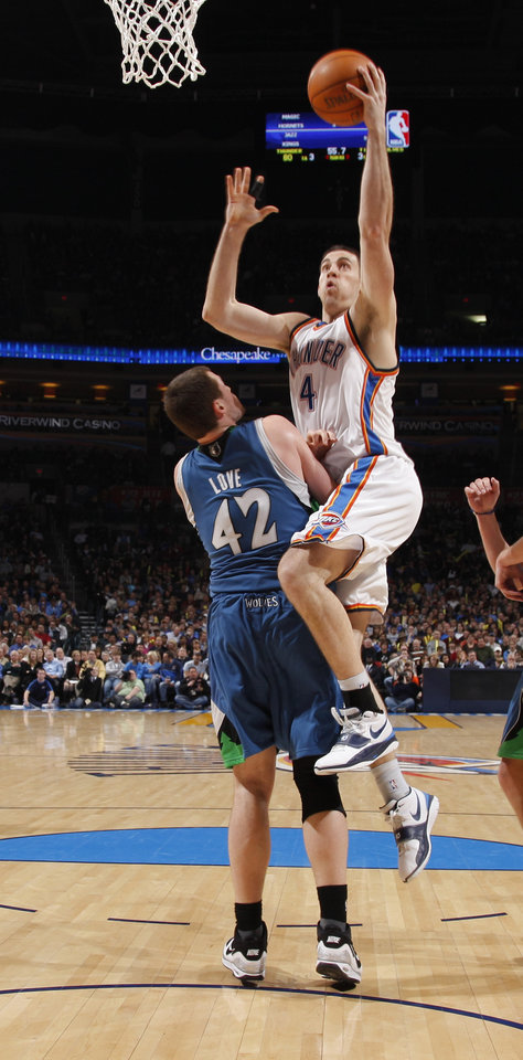 Photo - Oklahoma City's Nick Collison goes past Minnesota's Kevin Love during the NBA basketball game between the Oklahoma City Thunder and the Minnesota Timberwolves, at the Ford Center in Oklahoma City, Friday, Feb. 26, 2010.  Photo by Bryan Terry, The Oklahoman ORG XMIT: KOD