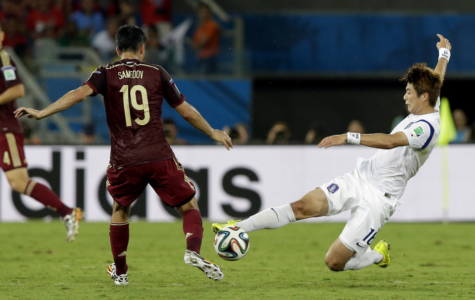 Photo - South Korea's Kim Shin-wook, right, challenges Russia's Alexander Samedov during the group H World Cup soccer match between Russia and South Korea at the Arena Pantanal in Cuiaba, Brazil, Tuesday, June 17, 2014. (AP Photo/Lee Jin-man)