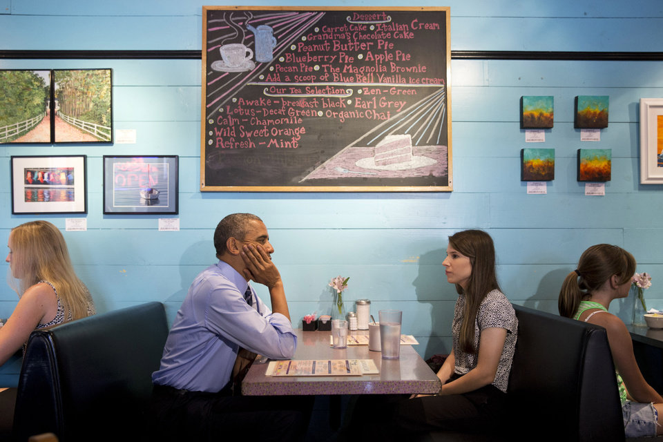 Photo - President Barack Obama meets with Kinsey Button, a student at the University of Austin, who wrote him a letter about her family, at Magnolia Cafe in Austin, Texas, Thursday, July 10, 2014. Obama will also speak about the economy at the Paramount Theater. Austin is the final leg in his three city trip before returning to Washington. (AP Photo/Jacquelyn Martin)