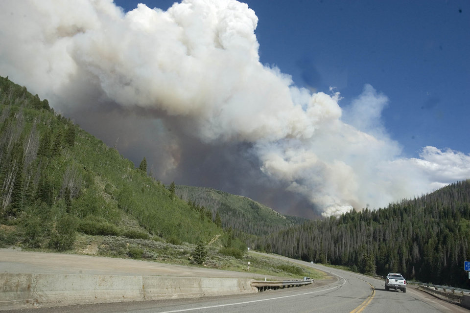 Photo -   A truck drives down state road 31 as smoke rises from a wildfire burning in the Manti-La Sal National Forest in Utah, Wednesday, June 27, 2012. At least five wildfires burned across Utah on Wednesday, taxing resources as firefighters worked feverishly to gain control, with one in the central part of the state continuing to burn with little containment after destroying at least 56 structures, authorities said. (AP Photo/The Salt Lake Tribune, Paul Fraughton)