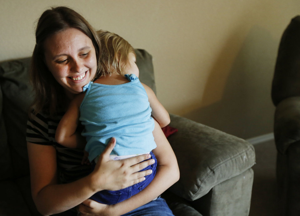 Photo - Haley Argyle holds her daughter Tinley, 1, at their home June 6 in Norman. Argyle's husband is deployed with the National Guard. Photo By Steve Gooch, The Oklahoman  Steve Gooch - The Oklahoman