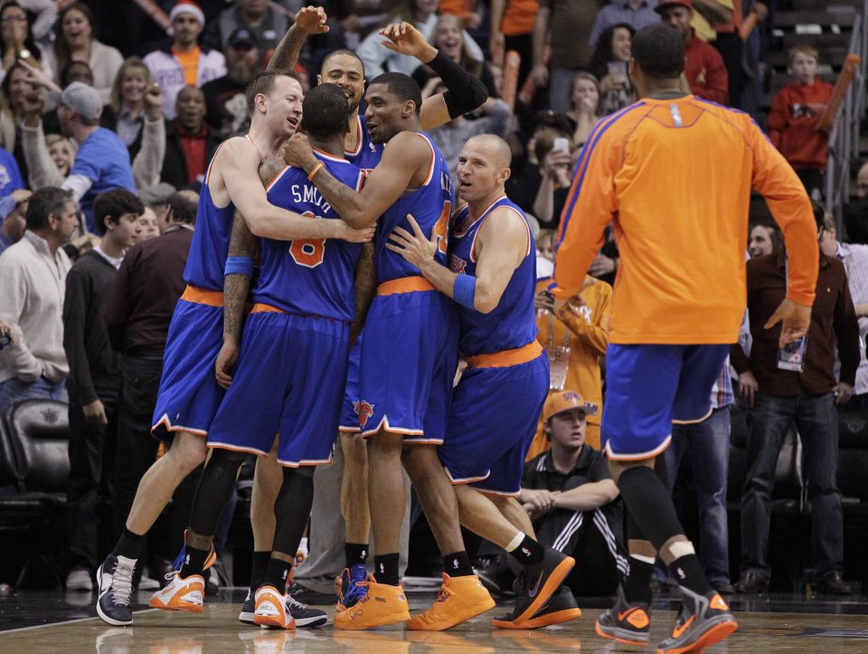 New York Knicks' Jason Kidd, right, James White (4), Steve Novak, left, and Tyson Chandler, rear, celebrate with teammate J.R. Smith after Smith hit a game-winning basket against the Phoenix Suns during the second half of an NBA basketball game on Wednesday, Dec. 26, 2012, in Phoenix. The Knicks won 99-97. (AP Photo/Matt York)