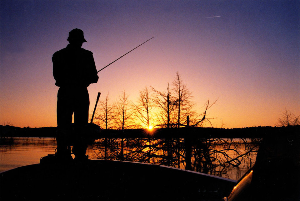 Photo - A sunset on McGee Creek in southeastern Oklahoma. McGee Creek was one of 44 Oklahoma lakes this year to be stocked with the Florida-strain largemouth bass. Big bass producing lakes like McGee Creek are stocked each year with Floridas, which grow faster and larger than native largemouth bass. PHOTO BY ED GODFREY, THE OKLAHOMAN  By Ed Godfrey, The Oklahoman