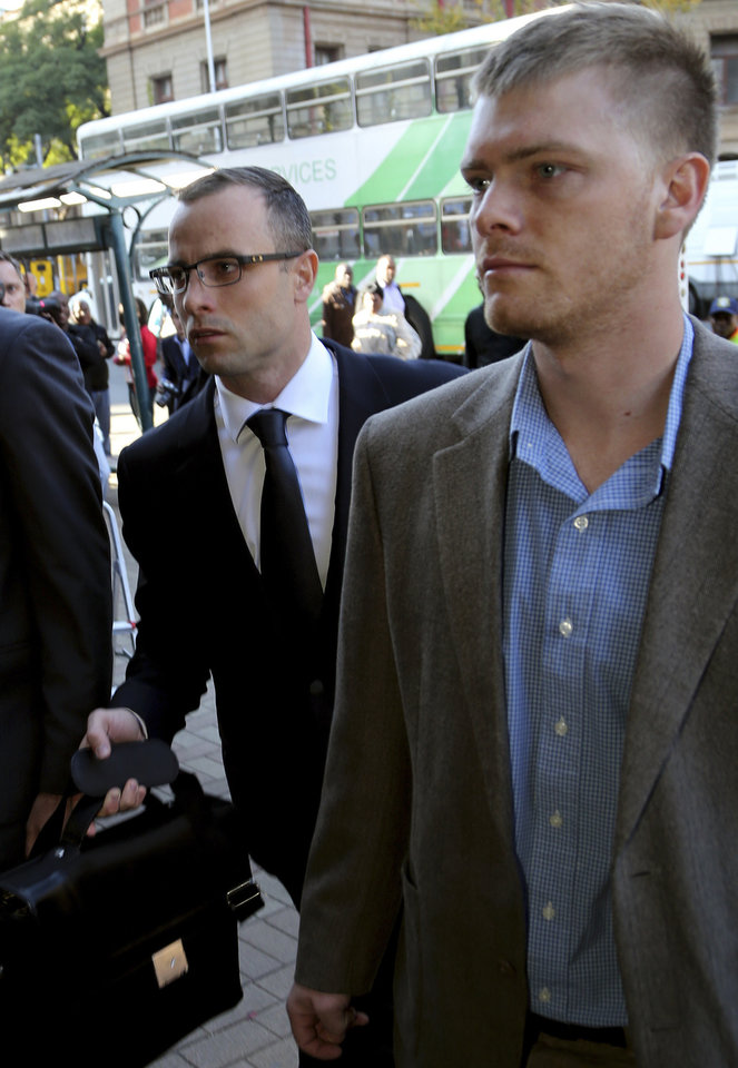 Photo - Oscar Pistorius, left, accompanied by an unidentified relative, walks towards the high court in Pretoria, South Africa, Wednesday, May 14, 2014. The chief prosecutor in the murder trial of Pistorius on Tuesday asked that the double-amputee runner be placed under psychiatric evaluation after an expert witness testified that he had an anxiety disorder. Pistorius is charged with murder for the shooting death of his girlfriend, Reeva Steenkamp, on Valentines Day in 2013. (AP Photo/Themba Hadebe)
