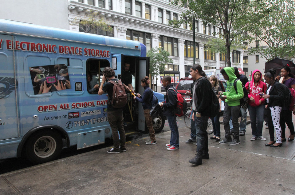 Photo -   In this Sept. 27, 2012 photo, students from New York's Washington Irving educational complex line up to leave their cellphones and other electronic devices, for a dollar a day per item, in a privately operated truck parked near their school. Cellphones are banned in all New York City public schools, but the rule is widely ignored except in schools with metal detectors. Outside those schools, entrepreneurs park trucks where students drop off devices before class and get them back at the end of the day.(AP Photo/Tina Fineberg)