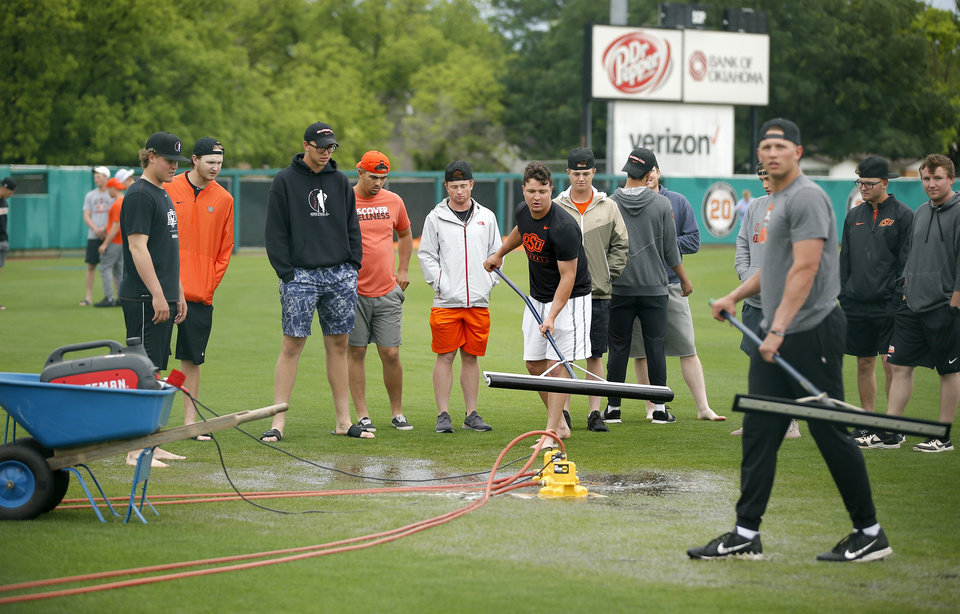 Photo - Members of the Oklahoma State baseball team try to clear water from the outfield before the scheduled baseball game against Baylor was cancelled in Stillwater, Okla., Saturday, May 18, 2019.  [Bryan Terry/The Oklahoman]