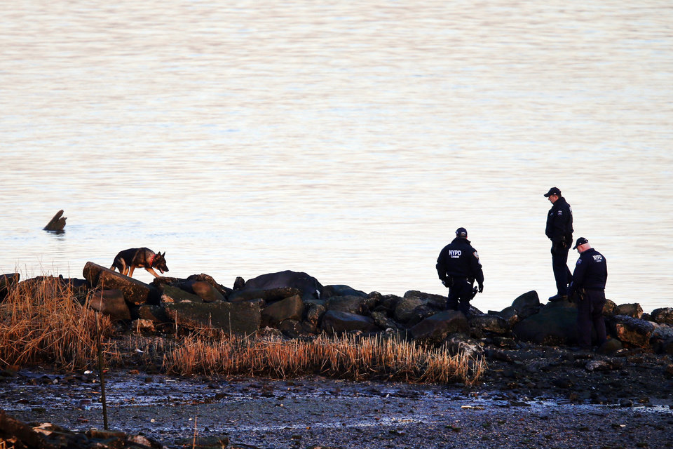 Photo - A New York Police Department canine unit continues the search for human remains after an arm and legs were discovered along a rocky shoreline in the Queens borough of New York, Friday, Jan. 17, 2014. Police were investigating whether human remains found along the shore of New York City's East River could be those of an autistic teen who walked out of his school and vanished more than three months ago, a law enforcement official said Friday. Fourteen-year-old Avonte Oquendo has been missing since Oct. 4, the day he walked out of his school. Authorities are not clear whether the remains found Thursday belong to the missing teen. They were discovered at least 11 miles driving distance from his school. (AP Photo/Jason DeCrow)