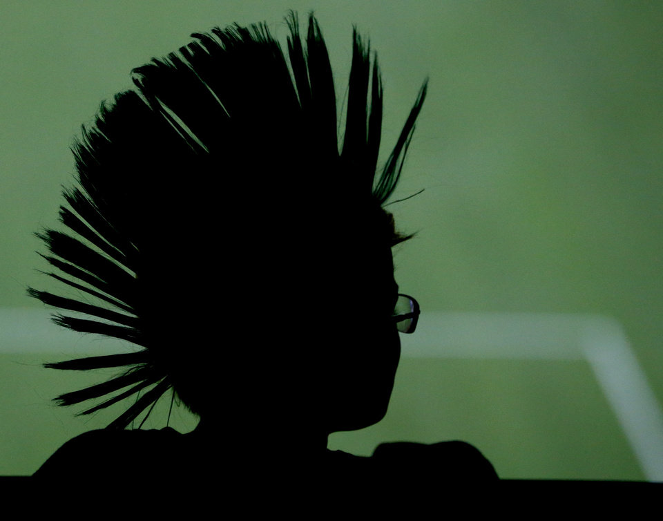 Photo - A spectator sports a mohawk-style wig while watching the second half of the World Cup opening match between Brazil and Croatia at Itaquerao Stadium in Sao Paulo, Brazil, Thursday, June 12, 2014. After taking the early lead in the opening match of the international soccer tournament, Croatia fell 3-1 to the five-time champion Brazil.  (AP Photo/Julio Cortez)