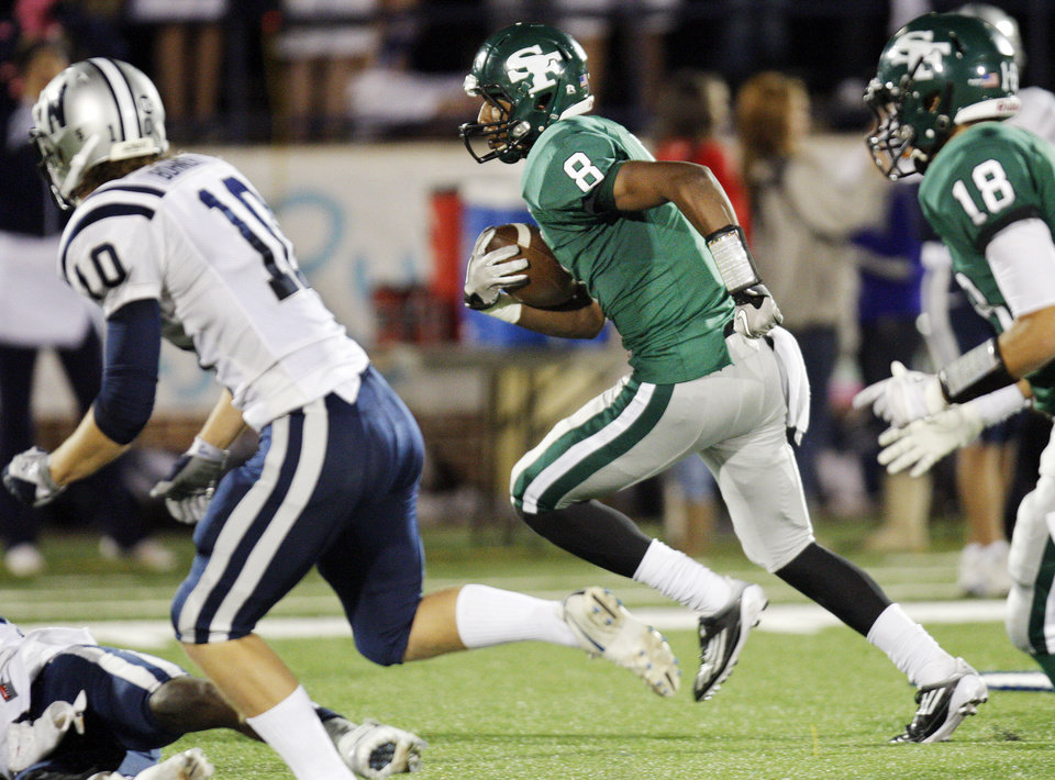 Photo - Edmond Santa Fe's Tre Kelley (8) runs after a catch near teammate Quintin James (18) and Camden Bohnert (10) of Edmond North during a high school football game between Edmond Santa Fe and Edmond North at Wantland Stadium in Edmond, Okla., Friday, Oct. 28, 2011. Photo by Nate Billings, The Oklahoman