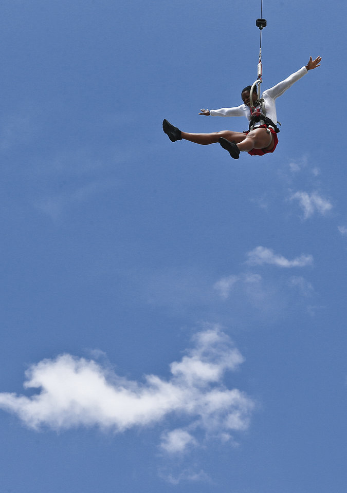Photo -  Evelyn Taylor floats with the clouds Thursday as she jumps from the Rumble Drop at OKC Riversport Adventures in Oklahoma City. Photo by Chris Landsberger, The Oklahoman   CHRIS LANDSBERGER -