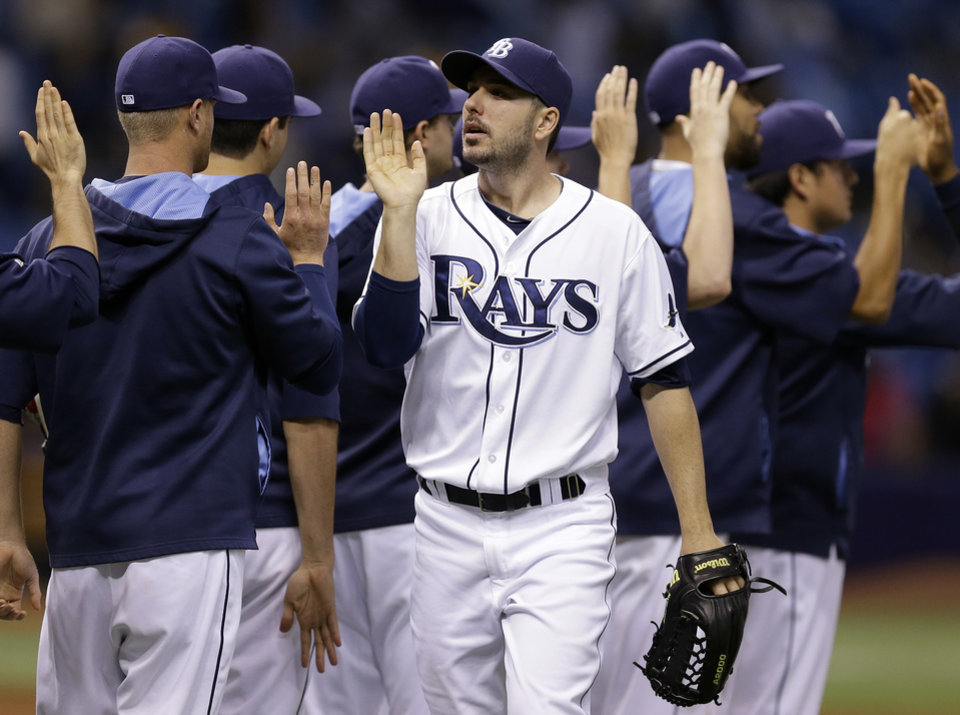 Photo - Tampa Bay Rays' Matt Joyce high fives teammates after the Rays defeated the Cleveland Indians 7-1 during a baseball game Saturday, May 10, 2014, in St. Petersburg, Fla. (AP Photo/Chris O'Meara)