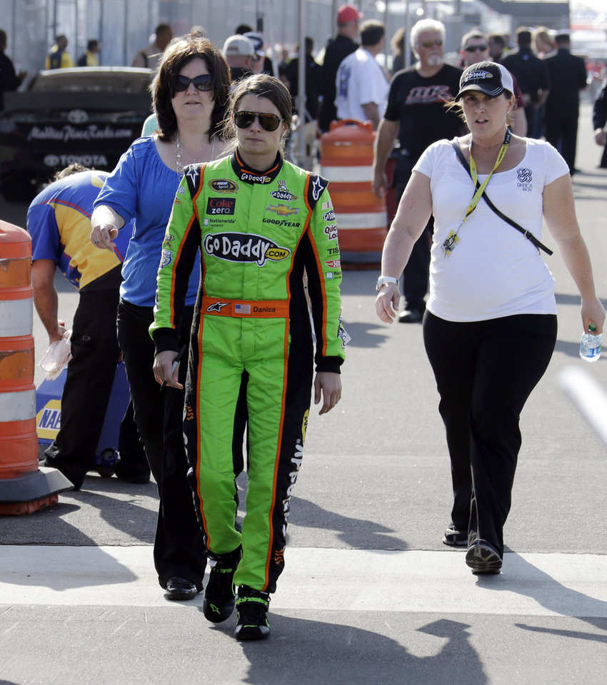 Danica Patrick walks to her car to qualify for the NASCAR Sprint Cup series auto race in Fontana, Calif., Friday, March 22, 2013. (AP Photo/Reed Saxon)