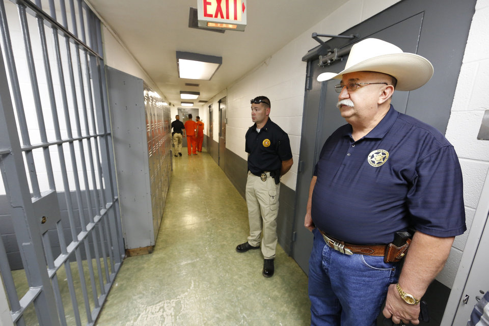 Photo - Canadian County Assistant Jail Administrator Lt. Travis Carmack and  Sheriff Randall Edwards wait to exit the jail in El Reno, Wednesday  September 4, 2013. Photo By Steve Gooch, The Oklahoman