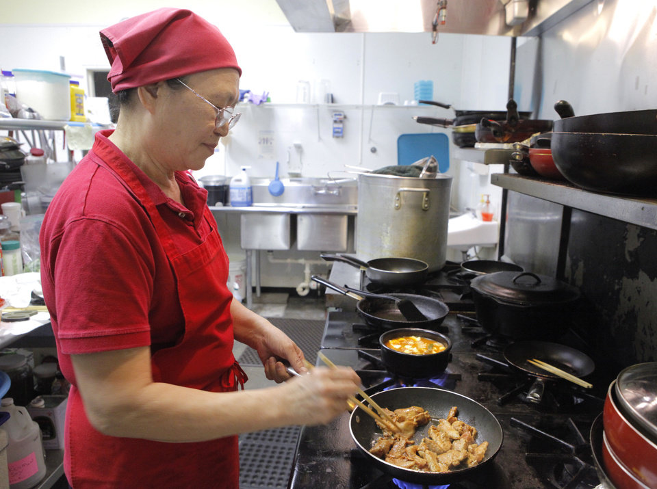 Owner Yong Rucker cooks Chicken Bulgogi. at Jeon Ju in Midwest City. <strong>David McDaniel - The Oklahoman</strong>