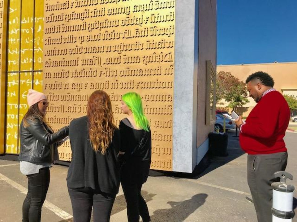 Photo - Camerin Oliphant, at right, reads material about the Museum of the Bible as his co-workers talk to a museum representative about the Gutenberg Gates replica outside Penn Square Mall on Saturday, Oct. 28 in Oklahoma City. [Photo by Carla Hinton, The Oklahoman]