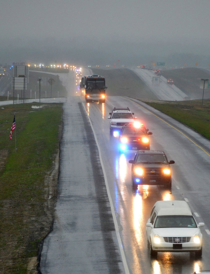 A motorcade of about 200 vehicles accompanies the white hearse carrying slain former Navy SEAL Chris Kyle's flag-draped coffin in Midlothian, Texas, Tuesday, Feb. 12, 2013, on the 200-mile journey to Austin, where he will be buried at the Texas State Cemetery. Many motorists pulled to the side of roads to watch the procession pass.Some 7,000 people attended a two-hour memorial service for Kyle at Cowboys Stadium in Arlington on Monday. Kyle and his friend Chad Littlefield were shot and killed Feb 2. at a North Texas gun range. (AP Photo/Waxahachie Daily Light, Scott Dorsett)