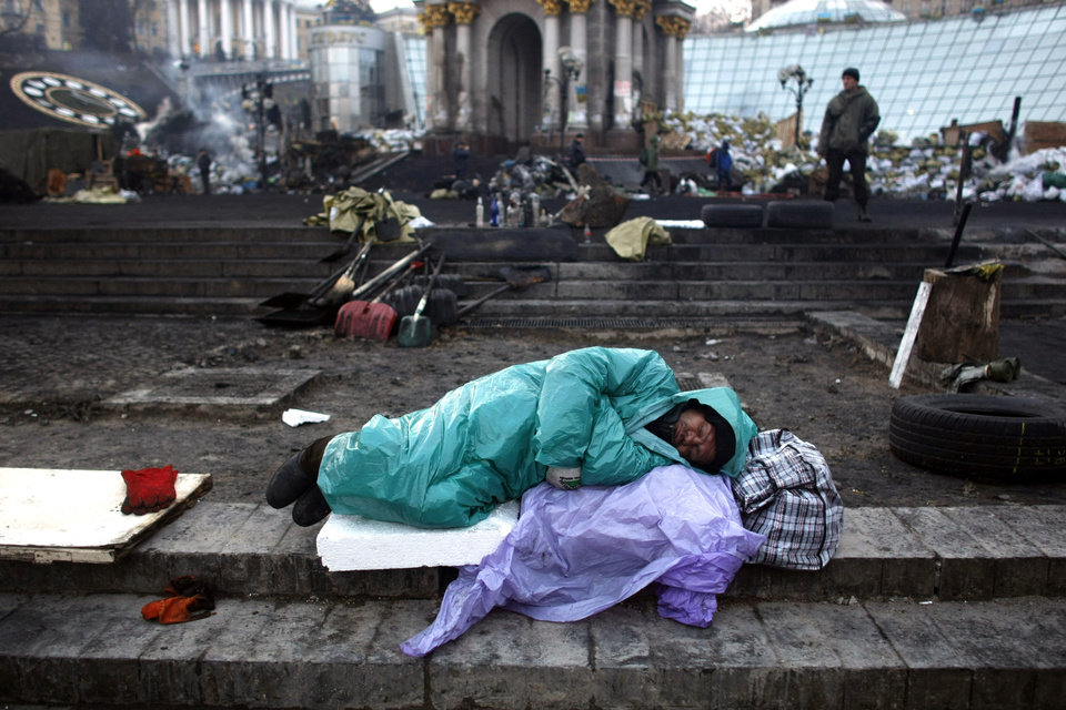 Photo - An anti-government protester sleeps at the Independence Square in Kiev, Ukraine, Friday, Feb. 21, 2014. Ukraine's presidency said Friday that it has negotiated a deal intended to end battles between police and protesters that have killed scores and injured hundreds, but European mediators involved in the talks wouldn't confirm a breakthrough. (AP Photo/ Marko Drobnjakovic)