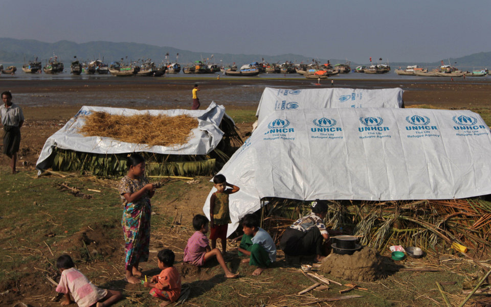 Photo - In this photo taken on Nov. 10, 2012, Kaman Muslim children play as a woman prepare food near their tent at Sin Thet Maw relief camp in Pauk Taw township, Rakhine state, western Myanmar. Stranded beside their decrepit flotilla of wooden boats, on a muddy beach far from home, the Muslim refugees tell story after terrifying story of their exodus from a once-peaceful town on Myanmar's western coast. The Oct. 24 exodus was part of a wave of violence that has shaken western Myanmar twice in the last six months.  (AP Photo/Khin Maung Win)