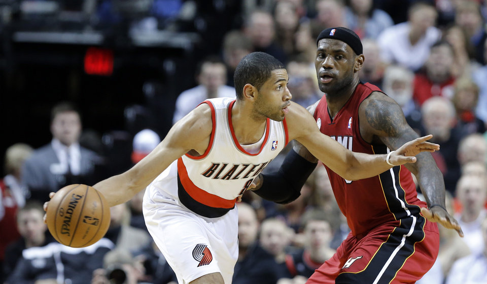 Portland Trail Blazers forward Nicolas Batum, left, from France, works the ball against Miami Heat forward LeBron James during the first quarter of an NBA basketball game in Portland, Ore., Thursday, Jan. 10, 2013. (AP Photo/Don Ryan)