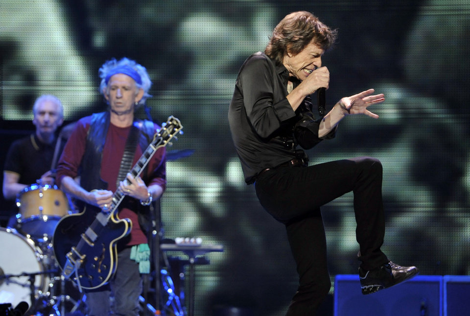 Photo - Mick Jagger, right, and bandmates Keith Richards, center, and Charlie Watts of the Rolling Stones perform on the kick-off of the band's